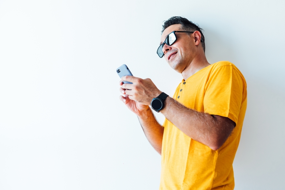 Modern man wearing yellow t-shirt and sunglasses, leaning on the wall, looks at his mobile phone
