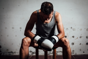 Portrait of a gloved boxer sitting on a bench at his training ground