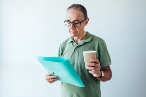 Entrepreneur retired man wearing a green shirt and glasses, holding a folder with a report and a coffee