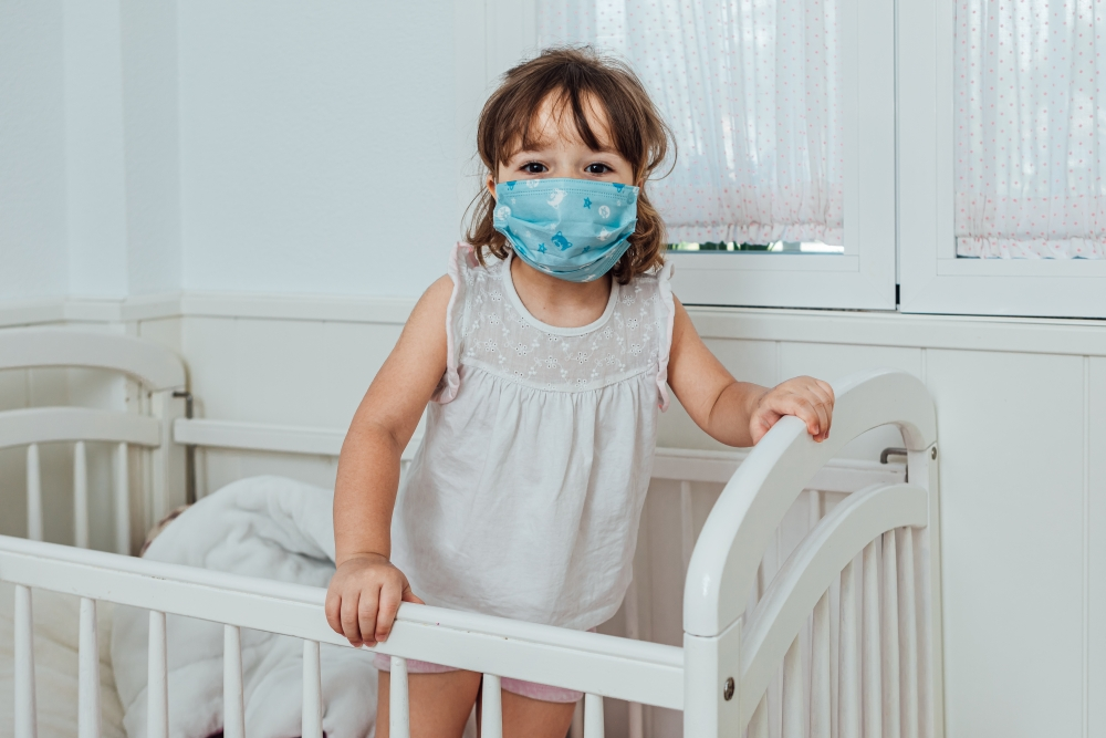 Doctor wearing a PPE attends a blonde little girl patient COVID-19 wearing a surgical mask in her crib at home