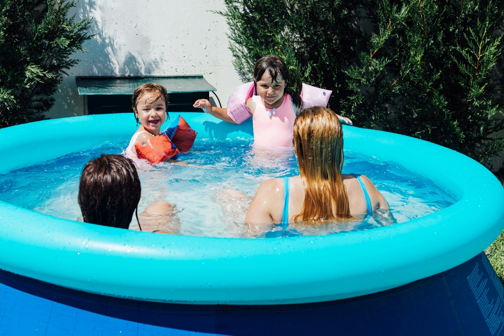 A couple of lesbian women bathe in the pool with their daughters