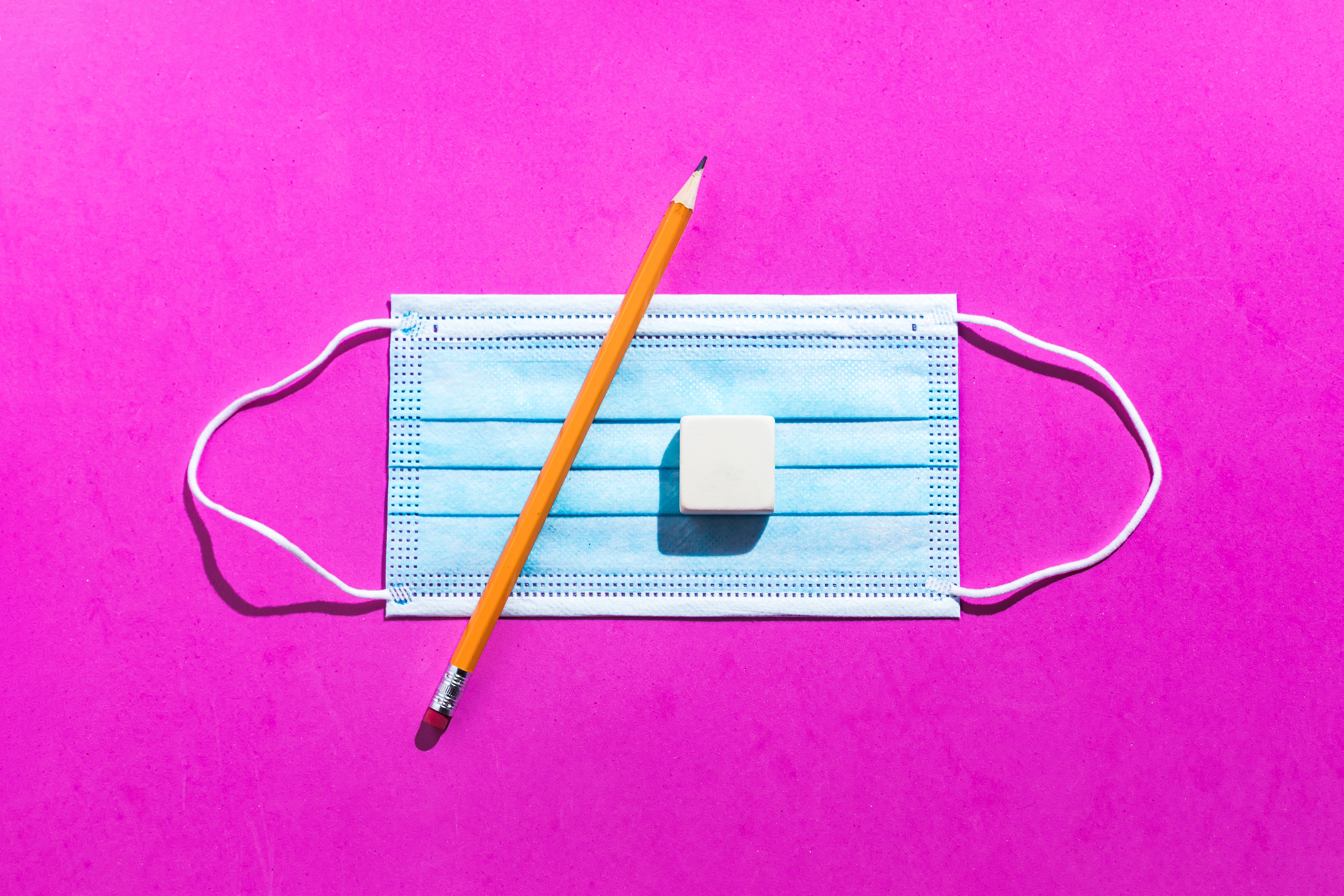 Pencil, surgical mask and eraser rubber from above on pink background. Office, school, coronavirus, COVID-19 and protective concept