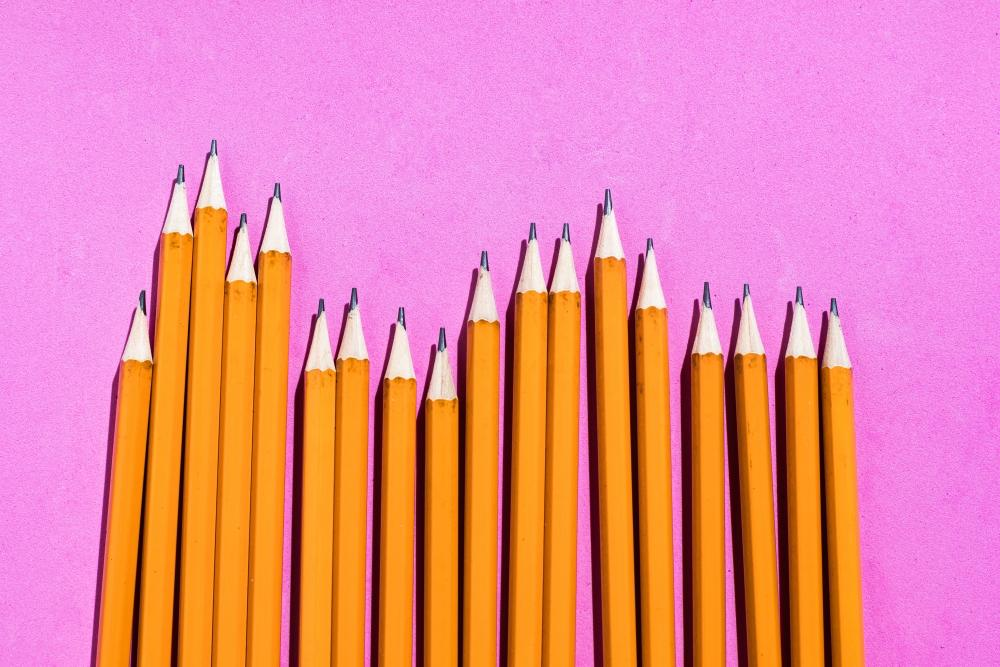 Pencils: pattern of orange pencils from above on pink background. Office and school concept