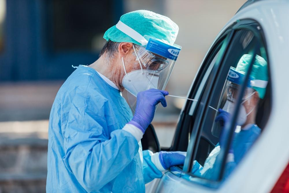 Medical personnel wearing a PPE, performing PCR with a swab in their hand, on a patient inside his car to detect if he is infected with COVID-19