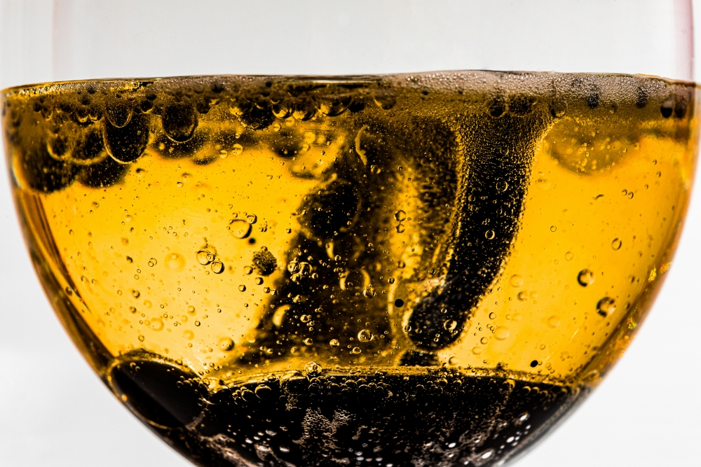 Glass cup with orange liquid and no with bubbles and ink