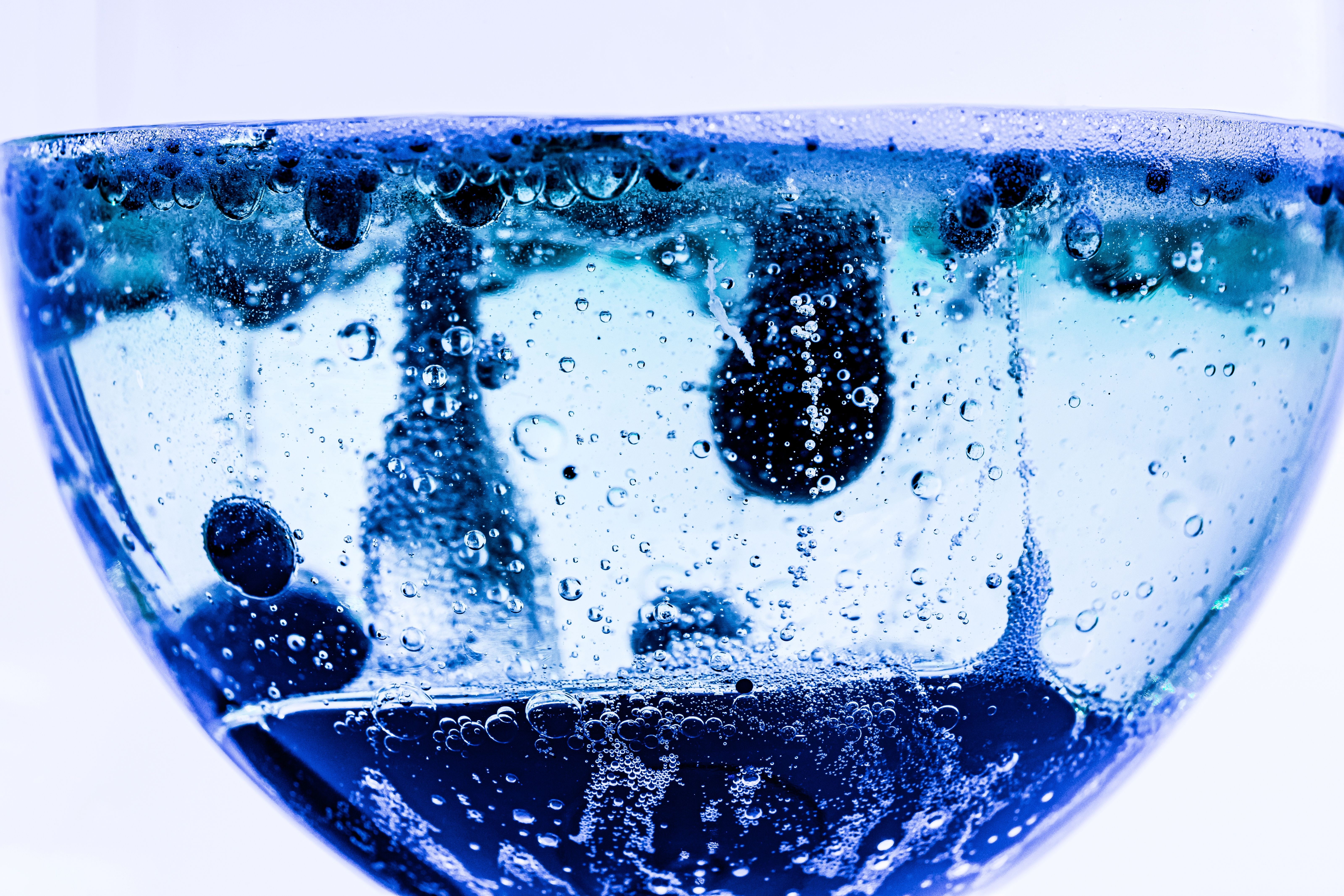 Glass cup with blue liquid and no with bubbles and ink