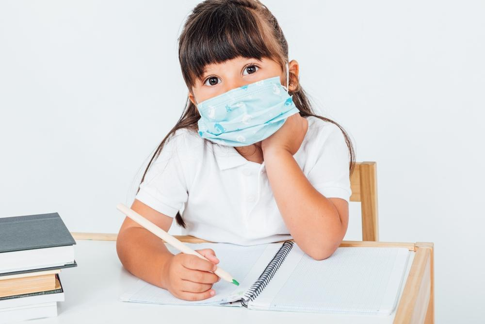 Brunette girl at school wearing a surgical mask to protect herself from COVID-19, sitting in a chair next to a table with books writing, on white background. School concept