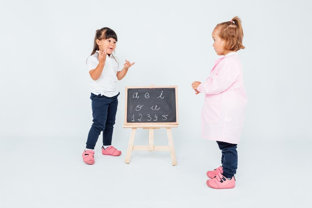 Two girls, one with black hair and the other with blonde hair, in class, next to a chalk board, sniffing and playing