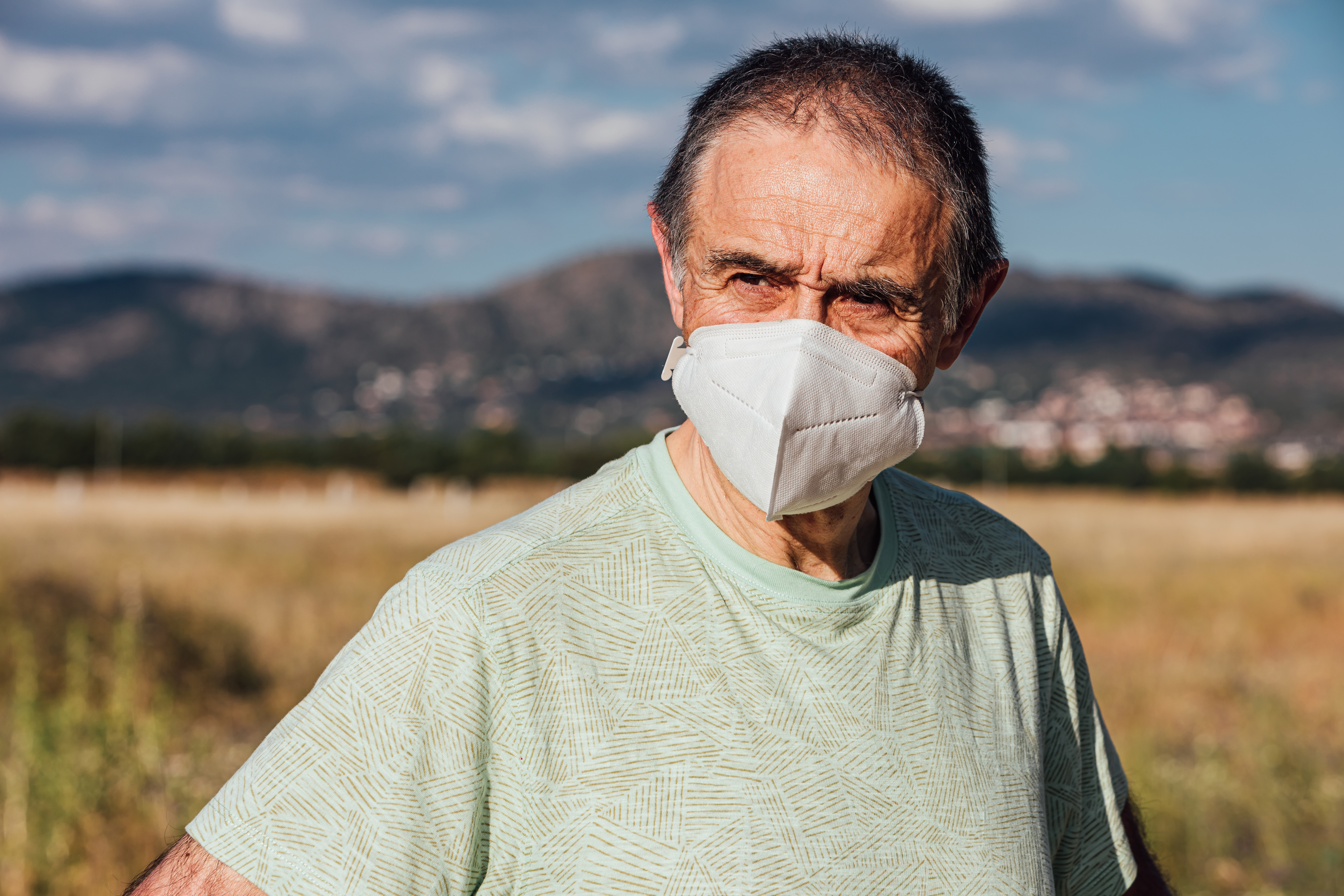 Portrait of senior man wearing face mask in field