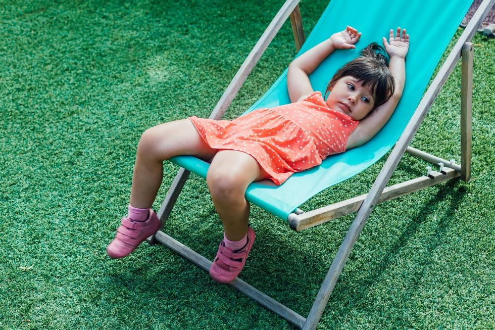 A black-haired girl lying on a lounger in the garden in summer
